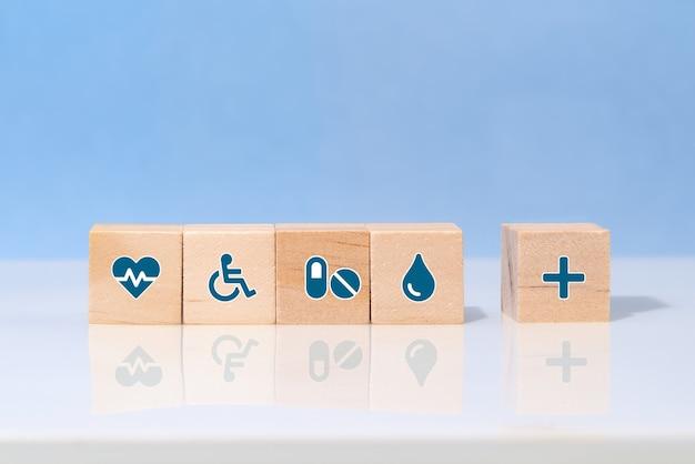 나무 블록에 이모티콘 아이콘 의료 의료 기호를 선택하십시오. 의료 및 의료 보험 개념
