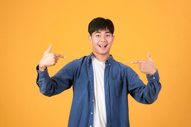 Выбери и выбери меня. уверенный молодой человек указывая и продвигая себя. портрет азиатского молодого человека изолирован