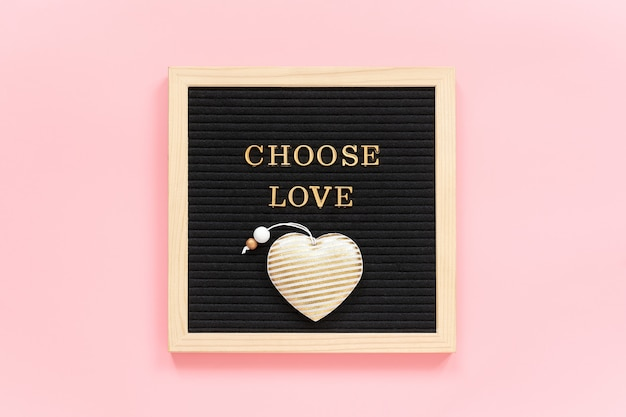 Choose love. motivational quote in gold letters and textile heart on black letter board on pink background.