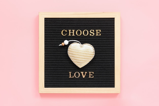 Choose love. motivational quote in gold letters and textile heart on black letter boardstcard. top view