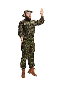 私を選んで。フルレングスの白いスタジオの背景に分離されたジャンプ迷彩服を着ている若い陸軍の兵士。若い白人モデル。軍事、兵士、軍のコンセプトです。専門的な概念