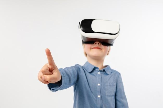 違いを選択してください。白いスタジオの背景に分離された仮想現実のメガネで空のスペースを指している小さな女の子や子供。最先端技術、ビデオゲーム、イノベーションのコンセプト。