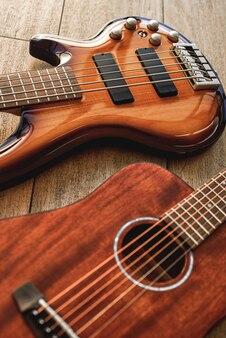 Выбираем гитару ... вид сверху на два идеально отполированных музыкальных инструмента: акустическая и электрогитара, лежащие на деревянном полу в музыкальном магазине. музыкальные инструменты. музыкальная концепция. корпус гитары