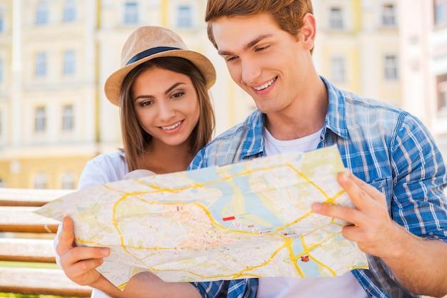 방문하기 좋은 곳을 선택합니다. 함께 벤치에 앉아 지도를 검토하는 행복한 젊은 관광 커플