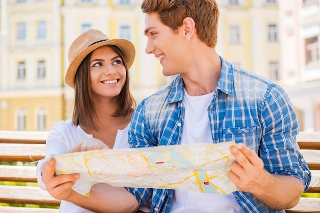 Выбор места, куда поехать. счастливая молодая туристическая пара, сидящая на скамейке вместе и изучающая карту