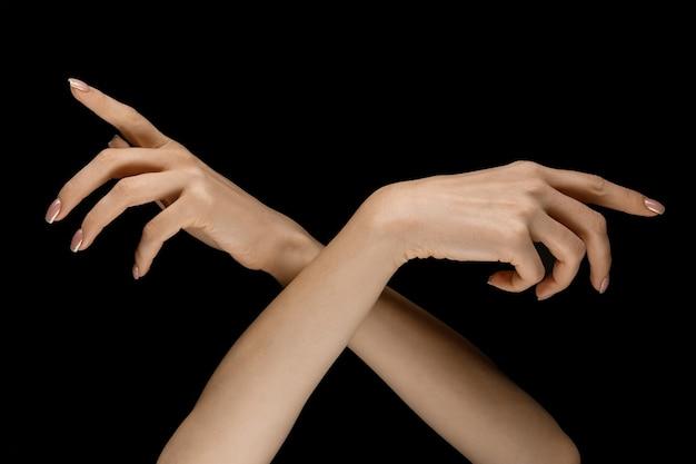 올바른 방법 선택. 검은 스튜디오 배경에 고립 된 터치를 얻는 제스처를 보여주는 남성과 여성의 손. 인간 관계, 관계, 감정 또는 비즈니스의 개념.