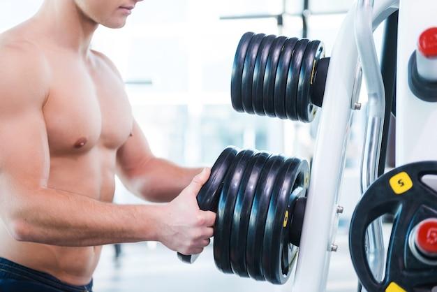 適切な体重を選択する。ジムに立っているときに運動するための体重を選択する筋肉の男のクローズアップ