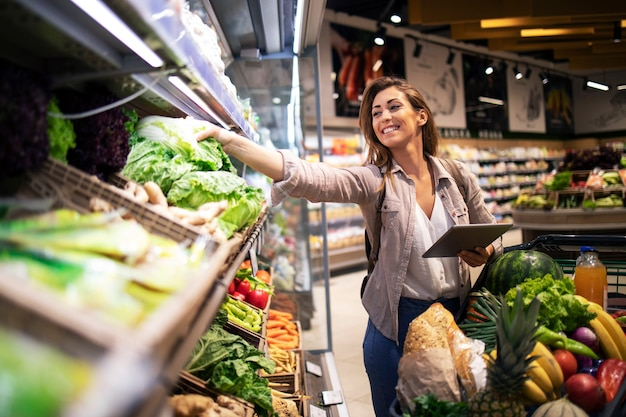 食料品店の棚で最高の野菜を選ぶ