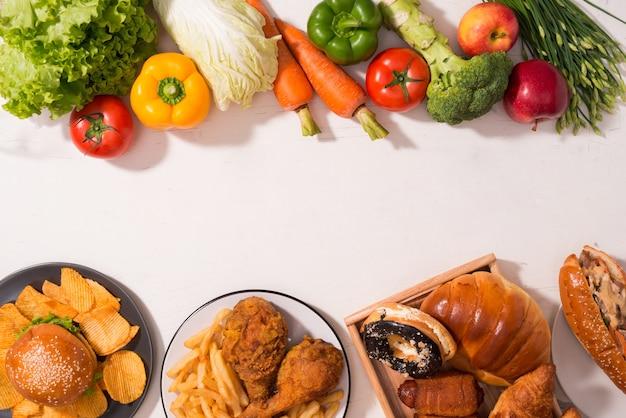 Выбор между фруктами и сладостями. здоровая пища против нездоровой. потеря веса. нездоровые соблазнительные торты и полезные фрукты