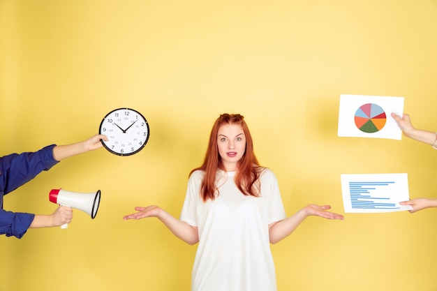 Choosing. caucasian young woman's portrait on yellow studio background, too much tasks. how to manage time right. concept of office working, business, finance, freelance, self management, planning.