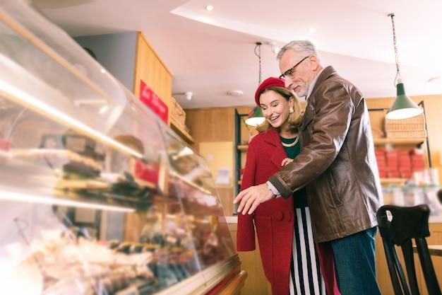 디저트 선택. 멋진 빵집에서 프랑스 디저트를 선택하는 성숙한 남자와 여자의 세련된 커플 사랑