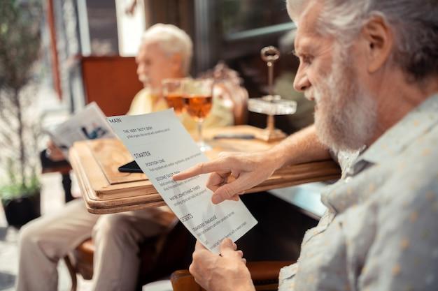 Choosing dish. close up of grey-haired bearded man holding menu and choosing dish
