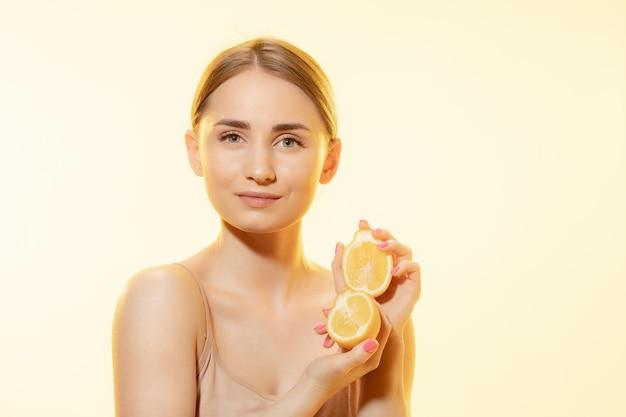 エコを選ぶ。レモンスライスと美しい女性の顔のクローズアップ