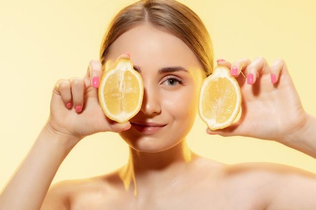 Выбираем эко. крупным планом красивое женское лицо с ломтиками лимона
