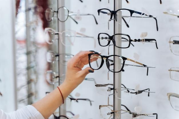 안경 선택. 광학 클라이언트입니다. 손에 선택적 초점입니다. 안경 스탠드에 교정 안경을 만지고 여자. 가게의 다양한 구색.