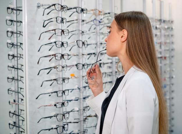 안경 선택. 광학 클라이언트입니다. 선택적 초점입니다. 카메라를 찾고 여자입니다. 안경을 쓰고 서십시오. 가게의 다양한 구색.