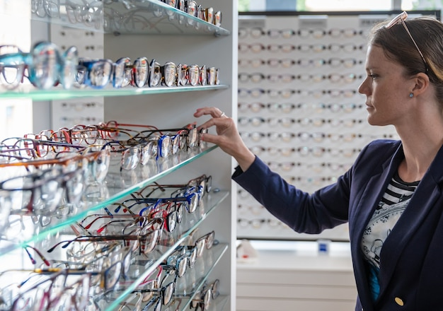 Choosing glasses in optics store by young woman