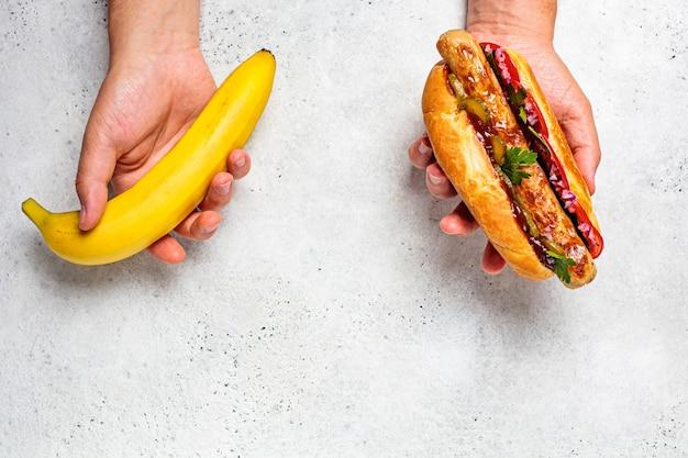 건강에 좋은 음식과 건강에 해로운 음식 개념을 선택합니다. 비건 대 육류 식사. 남성 손에 바나나와 핫도그.