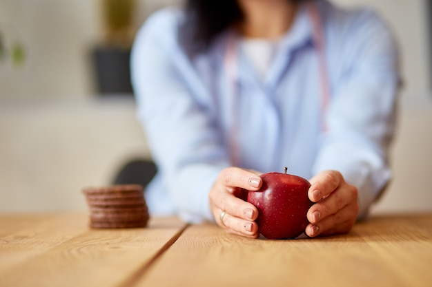 Выбирая здоровую или вредную концепцию, женщина отказывается от нездоровой пищи или нездоровой пищи, такой как печенье или десерт, и выбирает здоровую пищу, такую как свежее красное яблоко. велнес или диета.