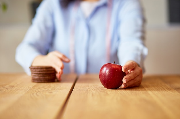건강 또는 정크 개념을 선택하는 여성, 쿠키나 디저트와 같은 정크 푸드나 건강에 해로운 음식을 거부하고 신선한 빨간 사과와 같은 건강 식품을 선택합니다. 웰빙 또는 다이어트.
