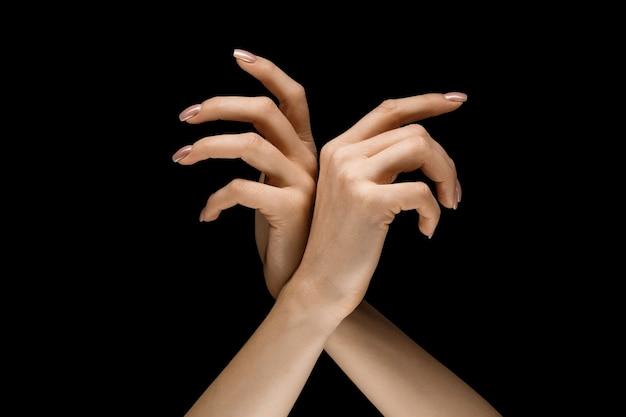 Scegliere un modo giusto. mani maschili e femminili che dimostrano un gesto di ottenere il tocco isolato su sfondo nero studio. concetto di relazioni umane, relazioni, sentimenti o affari.