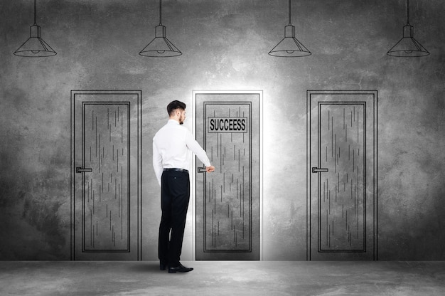 Choosing success. rear view of young man in formalwear openning an illustrated door