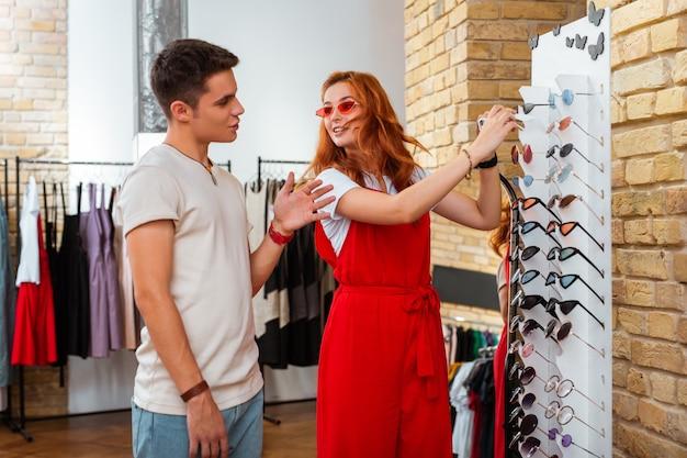 Выбираем солнцезащитные очки. эмоциональная милая пара обсуждает последнюю моду и примеряет солнцезащитные очки во время покупок