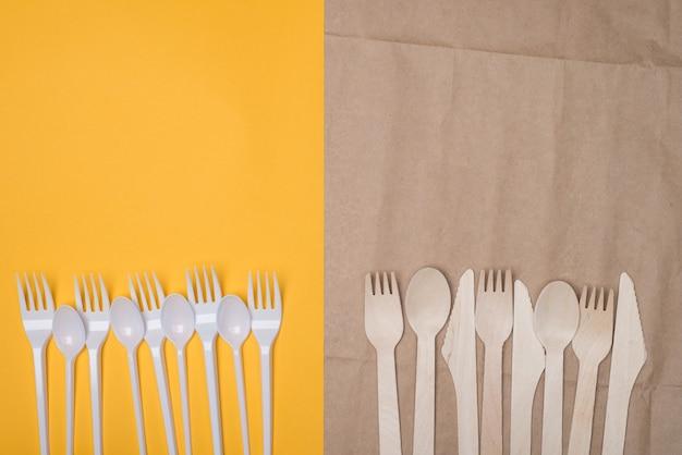 Выбор концепции экологически чистых столовых приборов. сверху сверху вид сверху фотографии белых пластиковых и деревянных столовых приборов по сравнению с изолированными на желтом и бумажном фоне