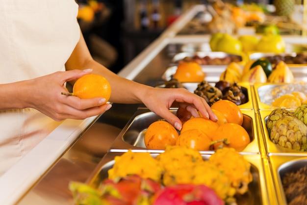 新鮮な果物を選ぶ。食料品店で果物を選ぶ女性のクローズアップ