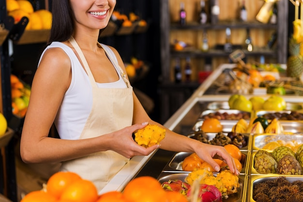 あなたのために最も新鮮な果物を選ぶ。さまざまな果物を背景に食料品店で働くエプロンの美しい若い女性のトリミングされた画像