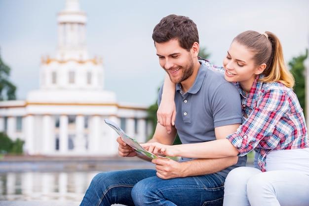 Выбор места, куда поехать. счастливая молодая туристическая пара, сидящая возле красивого здания и вместе изучающая карту
