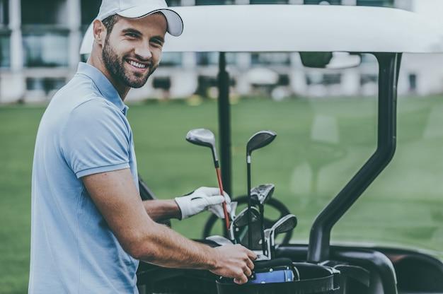 Выбор подходящего драйвера. красивый молодой мужчина в гольф выбирает водителя, стоя возле тележки для гольфа