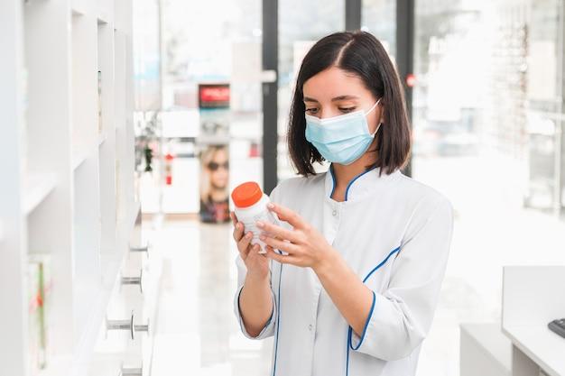Правильный выбор лекарства. профессионально выглядящая женщина-фармацевт в медицинской маске в аптеке изучает проспект нового лекарства.