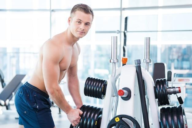 適切な重量の選択。自信を持って若い筋肉質の男性が持ち上げるために体重を選択し、ジムに立っている間笑顔