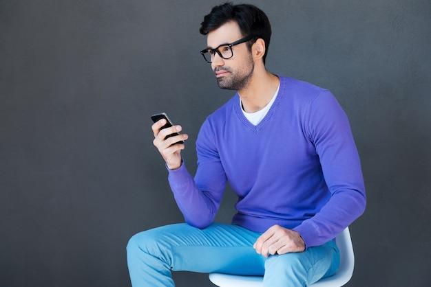 正しい言葉を選ぶ。携帯電話を保持し、灰色の背景に座って目をそらしているハンサムな若い男