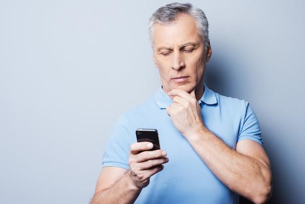올바른 단어 선택. 회색 배경에 서서 휴대폰을 들고 그것을 바라보는 티셔츠를 입은 진지한 성숙한 남자