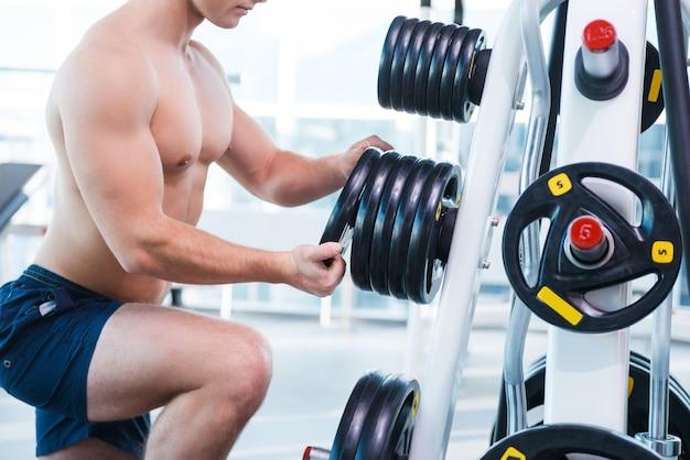 運動するための体重の選択。ジムに立っているときに運動するための体重を選択する筋肉の男のクローズアップ