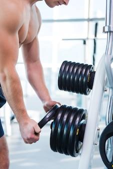 持ち上げる重量の選択。ジムに立っているときに運動するための体重を選択する筋肉の男のクローズアップ