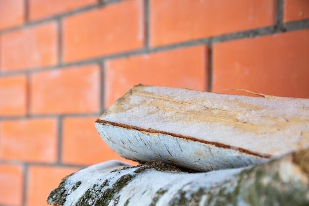 雪の中で刻んで積み上げた白樺の薪。背景の赤レンガの壁