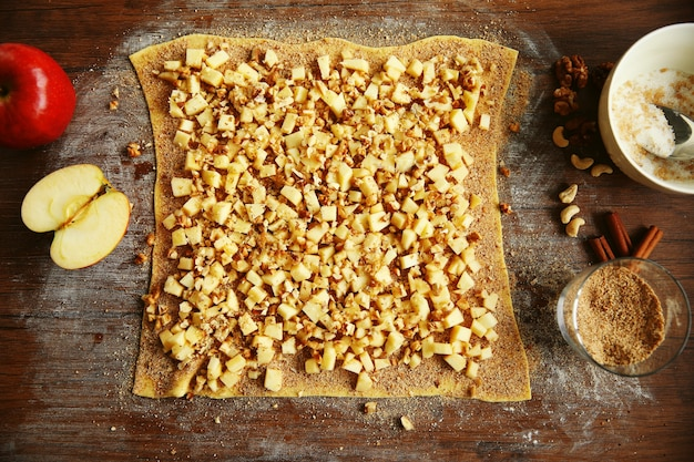 Нарезанные яблоки и тесто на кухонном столе