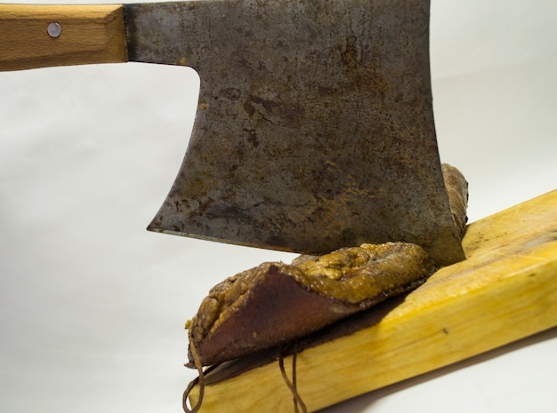Нарезанный бекон на деревянной доске железным топориком на белом фоне