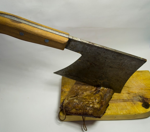 Chopped bacon on a wooden plank with an iron hatchet on a white background