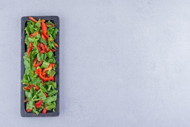 Нарезанный болгарский перец и кучу салата в небольшом подносе на мраморном фоне. фото высокого качества