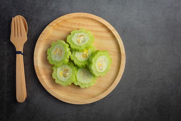Zucca amara tritata messa sul piatto di legno con cucchiaio e forchetta
