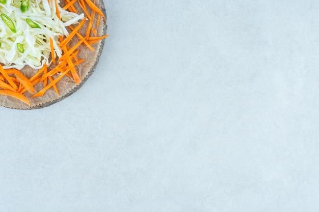 대리석 위에 보드에 다진 양배추와 당근.