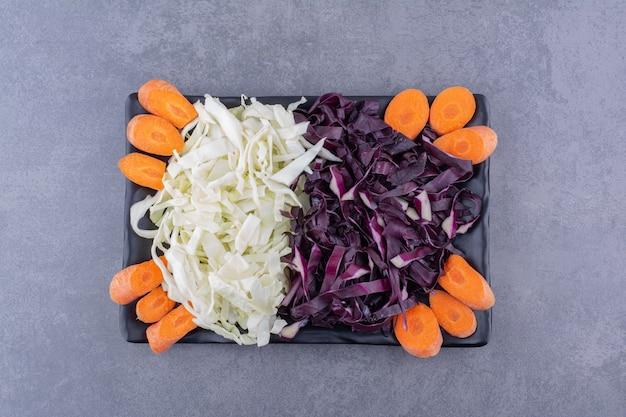 みじん切りのキャベツとにんじんのスライスを大皿に盛り付けます。