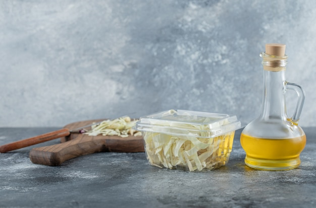 Cavolo tritato, bottiglia di olio su sfondo grigio. foto di alta qualità