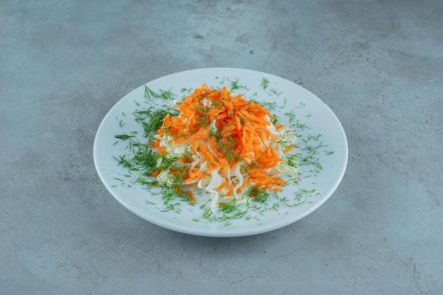 Cavolo e carote tritati sulla zolla bianca.