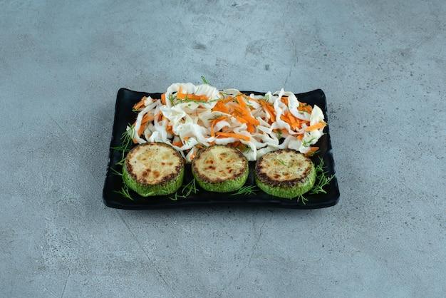 Cavolo e carote tritati con pepe alla griglia su banda nera.