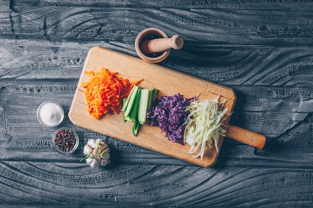 Chopped cabbage on a cutting board with other vegetables top view on a dark wooden background